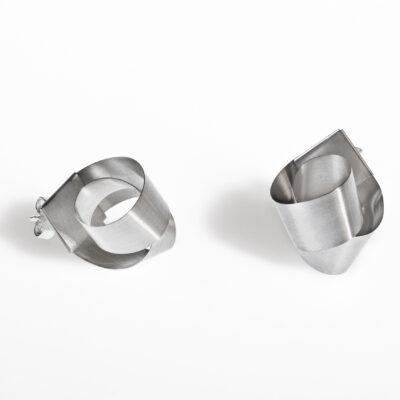 Die Ohrstecker BOW sind aus einem langen Silberstreifen gearbeitet, der um sich selbst gewunden zu einem Knoten wird.